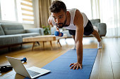 istock Young man using laptop and exercising at home 1276686246