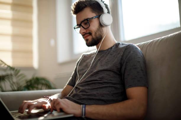 Junger Mann mit Laptop und Musikhören zu Hause – Foto