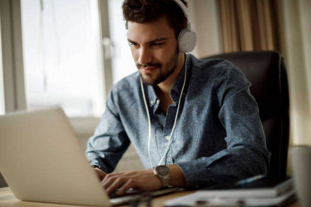 Young man using laptop and listening to music stock photo