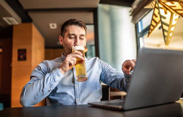 Young Man using laptop at bar