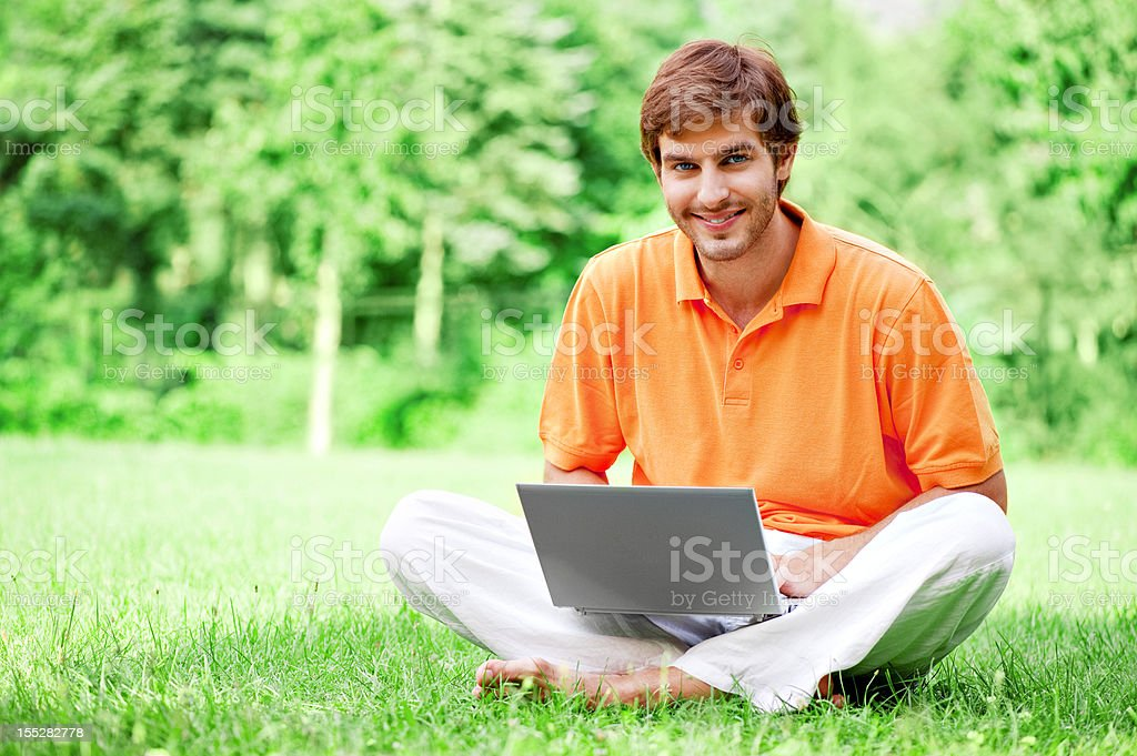 Young man using laptop at park royalty-free stock photo