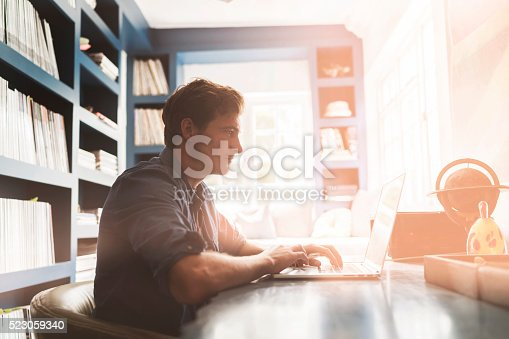 istock Young man using laptop at table 523059340