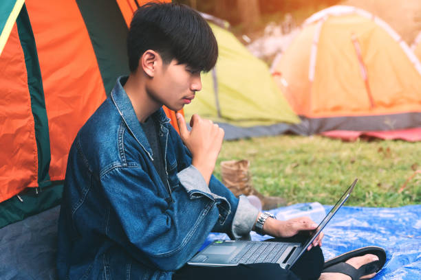 Young man using laptop during camping stock photo