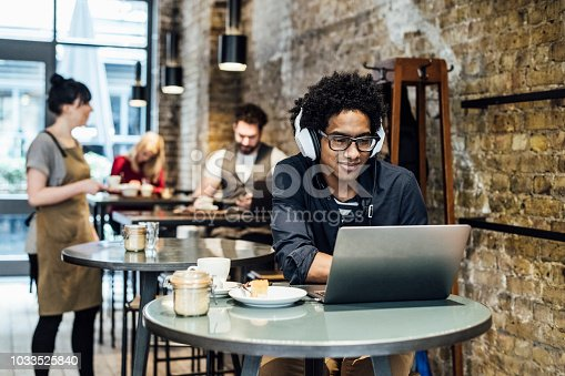 Male customer sitting at table wearing headphones, waitress serving people in the background
