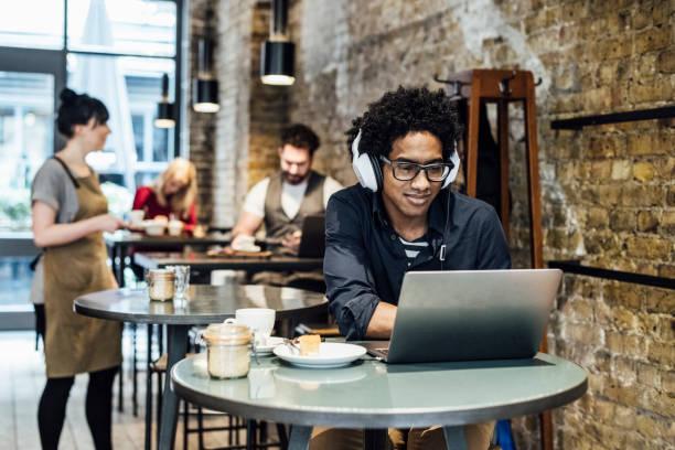 junger mann mit laptop im café und musik hören - cafe stock-fotos und bilder
