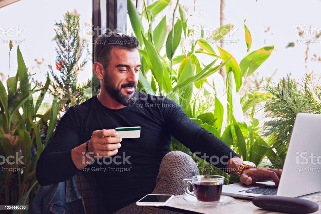 Kafede dizüstü bilgisayar kullanan genç adam stok fotoğrafı