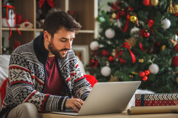 Young man using laptop in the living room near the Christmas tree stock photo
