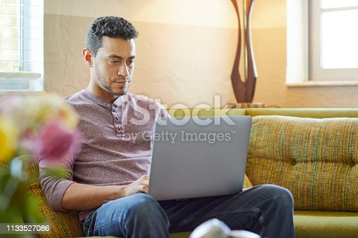 Young man using laptop at home. Male is sitting on couch in living room. He is wearing casuals.