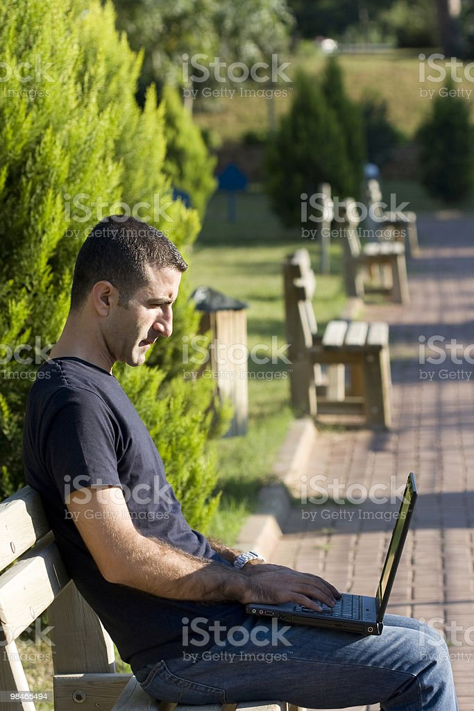 Young man using laptop on park bench royalty-free stock photo