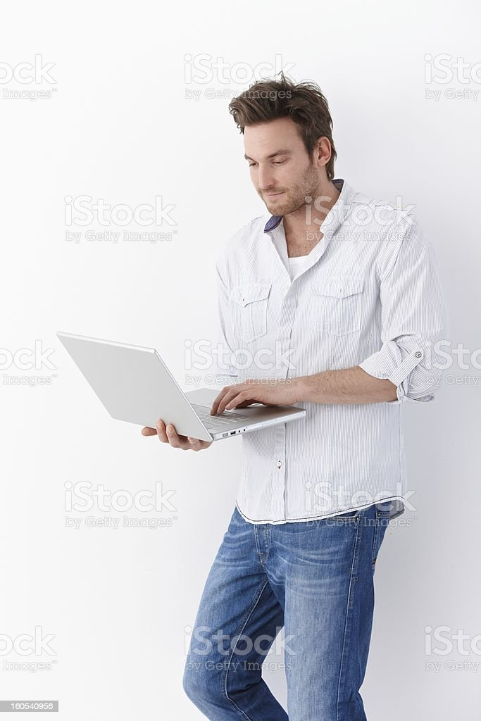 Young man using laptop standing smiling royalty-free stock photo