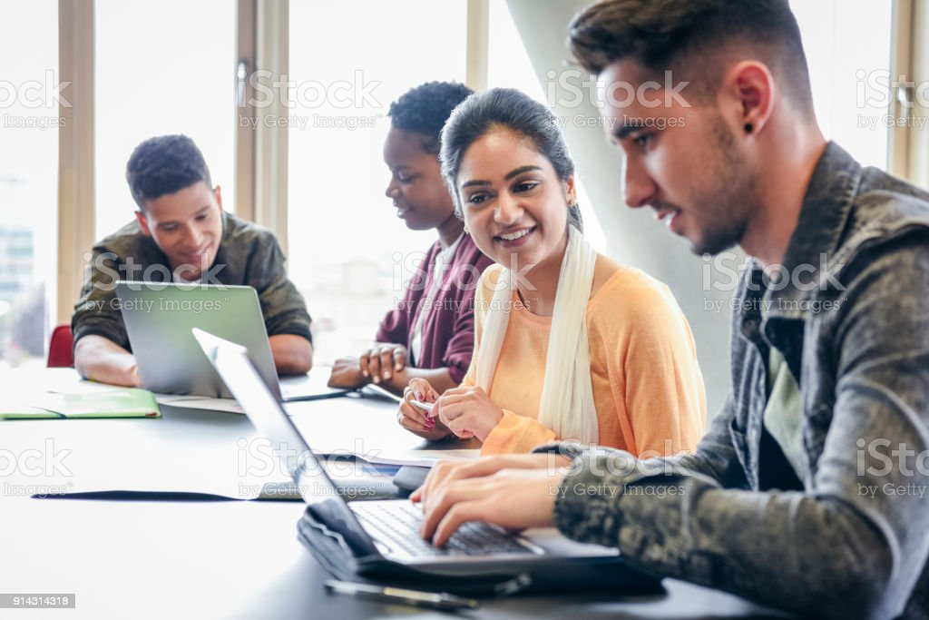 Jovem usando laptop com aluna olhando e sorrindo - Foto de stock de 20 Anos royalty-free
