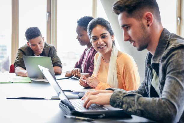 junger mann mit laptop mit studentin beobachten und lächelnd - england stock-fotos und bilder