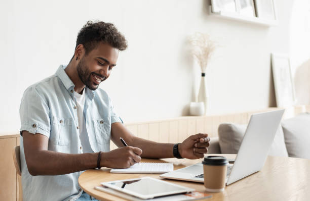Young man using laptop working at home, studying online stock photo