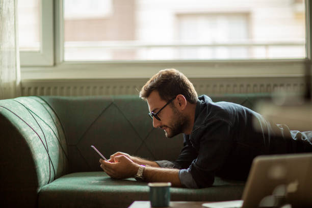Young man using mobile phone at home stock photo