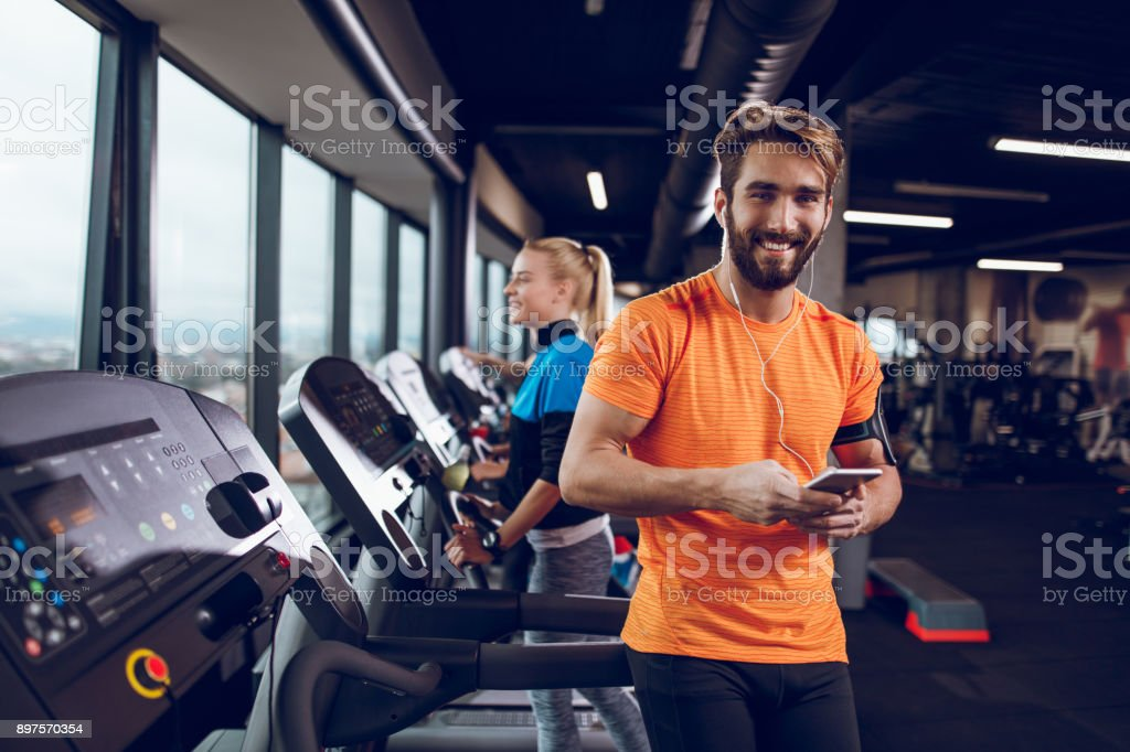 Young man using mobile phone while exercising on treadmill stock photo