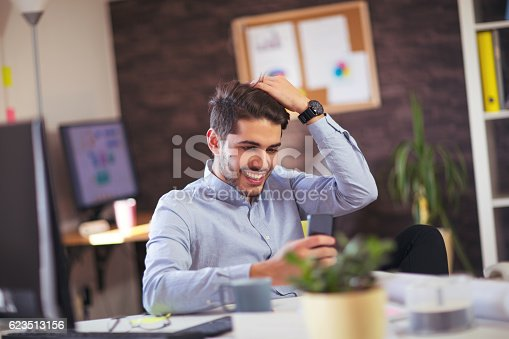 513583458 istock photo Young man using phone in office 623513156