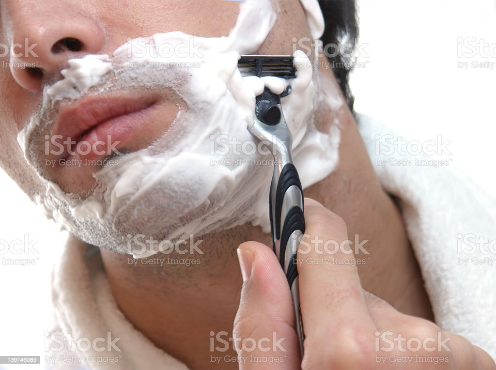 Young man using shaving cream and blade stock photo