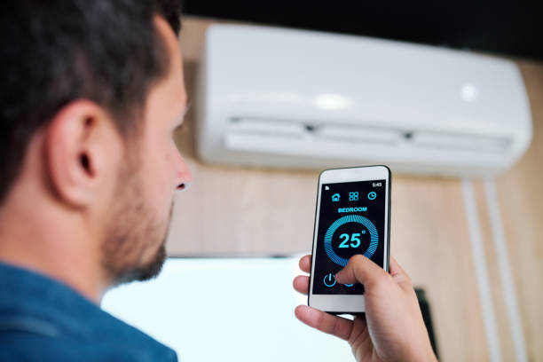 Young man using smart application to adjust temperature of air conditioner stock photo