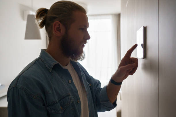 Young man using smart home touch screen technology device on wall Young man using smart home touch screen technology connected appliances device on wall monitoring energy security system digital control set comfort house room heating modern app, smart home concept smart thermostat stock pictures, royalty-free photos & images