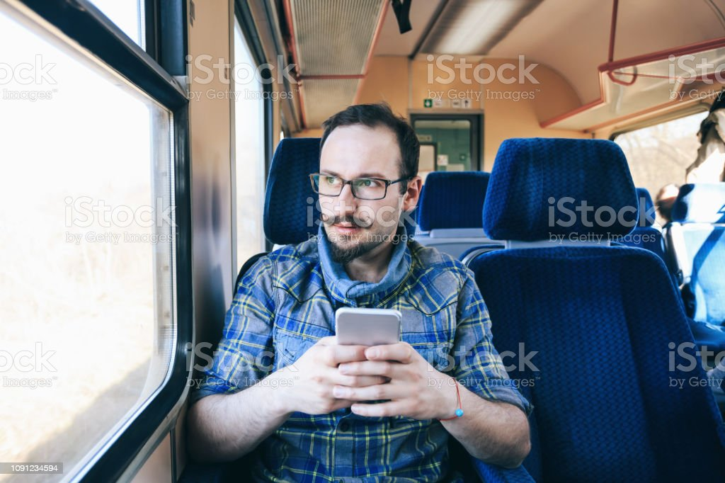 Smiling young man using smart phone inside of a trian