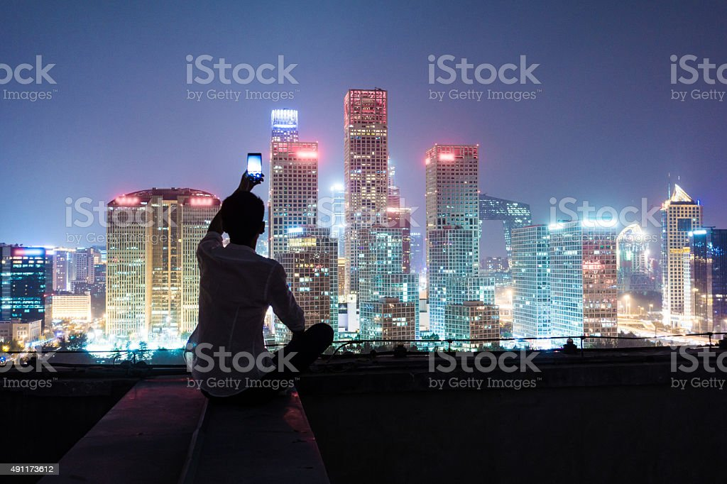 Young man using smart phone take photo in city night stock photo