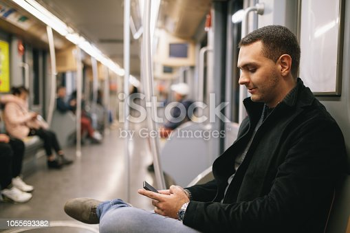 Young businessman using smart phone while riding the undergorund