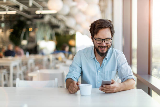 Young man using smartphone drinking coffee in a cafe stock photo