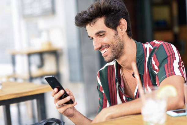Young man using smartphone in an urban cafe. stock photo