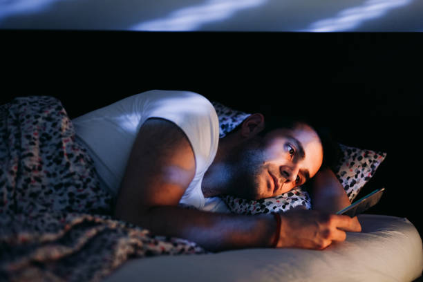 Young man using smartphone in bed at night stock photo