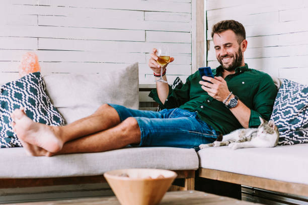 Young man using smartphone in the living room stock photo