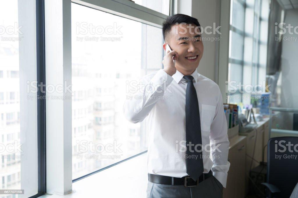 junger Mann mit Smartphone in der Nähe von Fenster – Foto