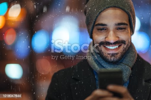 Young man using smartphone on city street on a snowy day