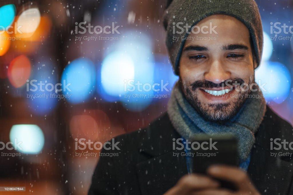 Junger Mann mit Smartphone auf Stadtstraße an einem verschneiten Tag – Foto