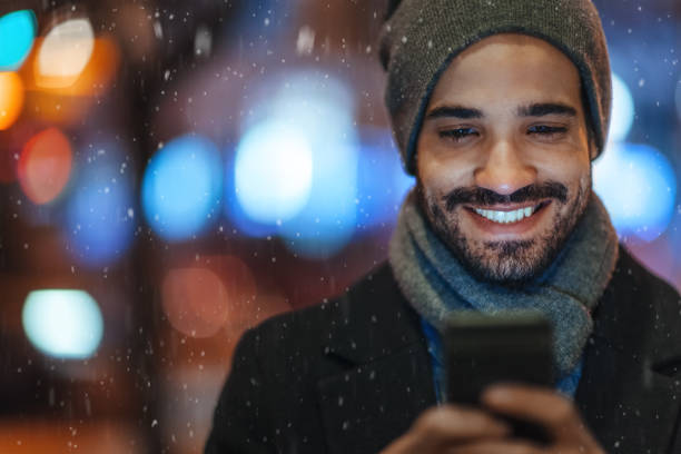 Young man using smartphone on city street on a snowy day stock photo