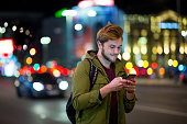 istock Young man using smartphone on urban street at night 1137581778