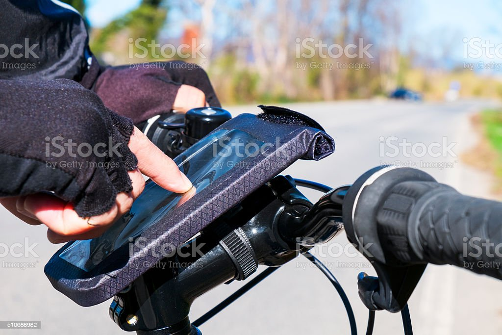 young man using  smartphone riding a bicycle stock photo