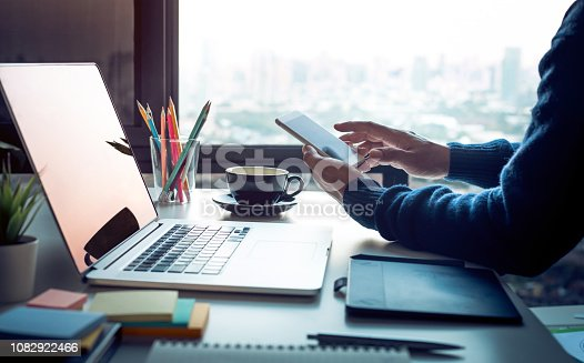 Young man using smartphone with modern work table and computer laptop and cityscapes view from window.Business concepts ideas.Strategy analysis.office life