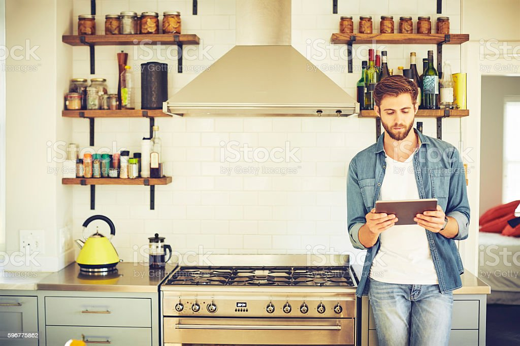 Young man using tablet computer in kitchen stock photo
