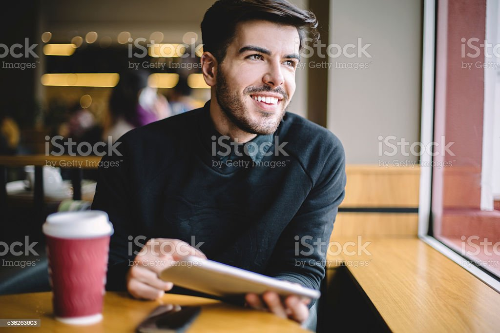 Young man using tablet in cafe stock photo