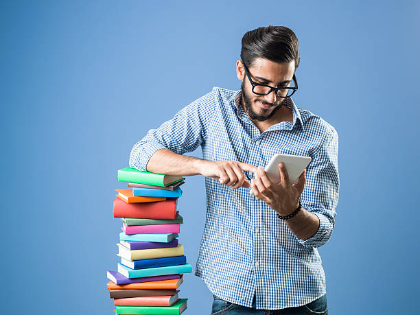 Young  Man Using Tablet Pc While Leaning On Books stock photo
