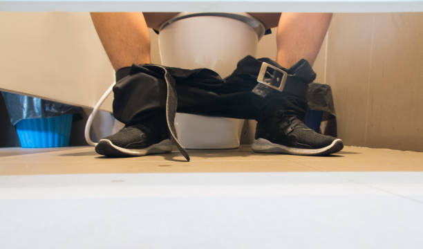 young man using toilet and removing his trousers down on the floor. - detract stock pictures, royalty-free photos & images