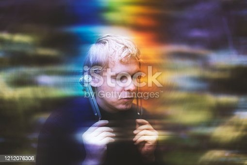 Young Man Using Tuning Fork in Forest with a Calm Face - Stock Photo