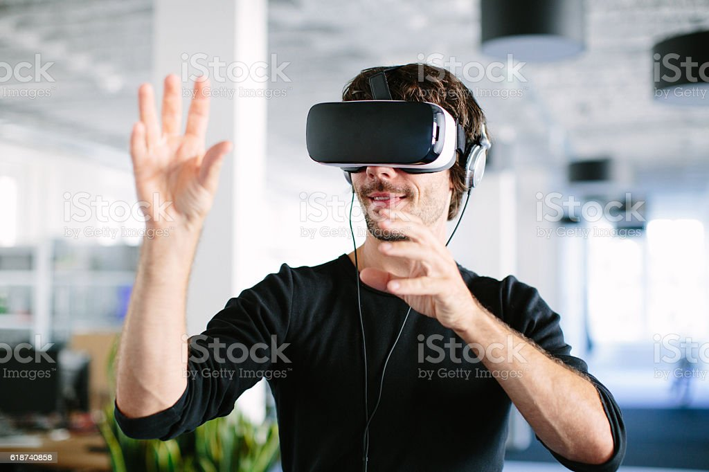 Young man using virtual reality glasses stock photo