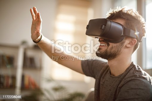 istock Young man using virtual reality simulator headset at home 1172208046