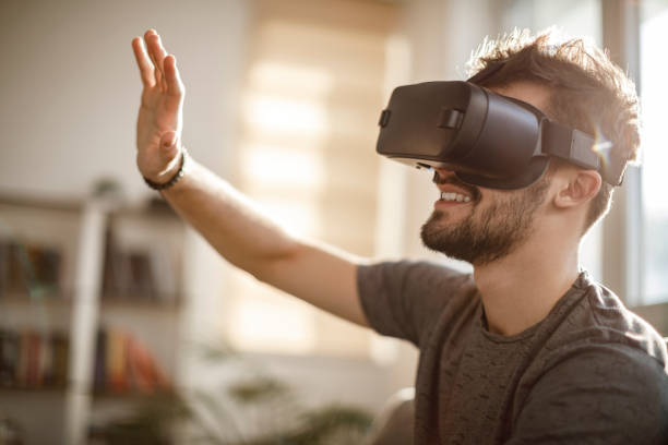 Young man using virtual reality simulator headset at home stock photo