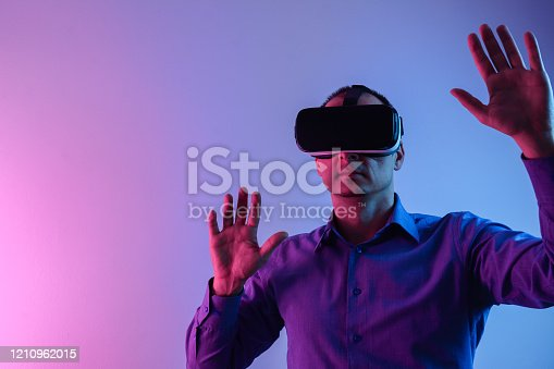 1090878574istockphoto Young man using virtual reality simulator, isolated on neon gel light. 1210962015