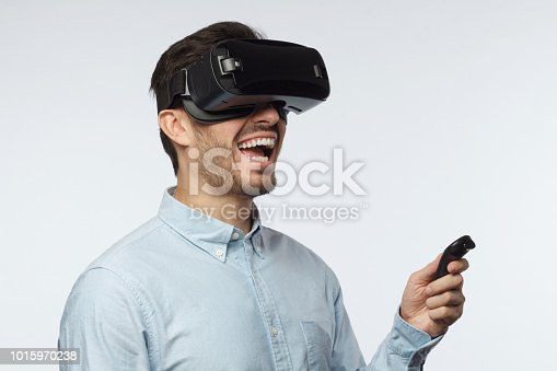 1090878574istockphoto Young man using vr headset, experiencing virtual reality while playing video game, using remote control with  hand 1015970238