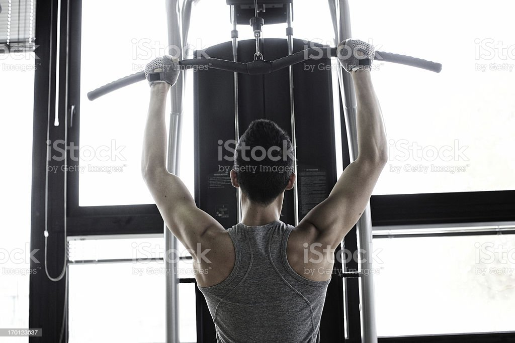 Young man using weight machine royalty-free stock photo