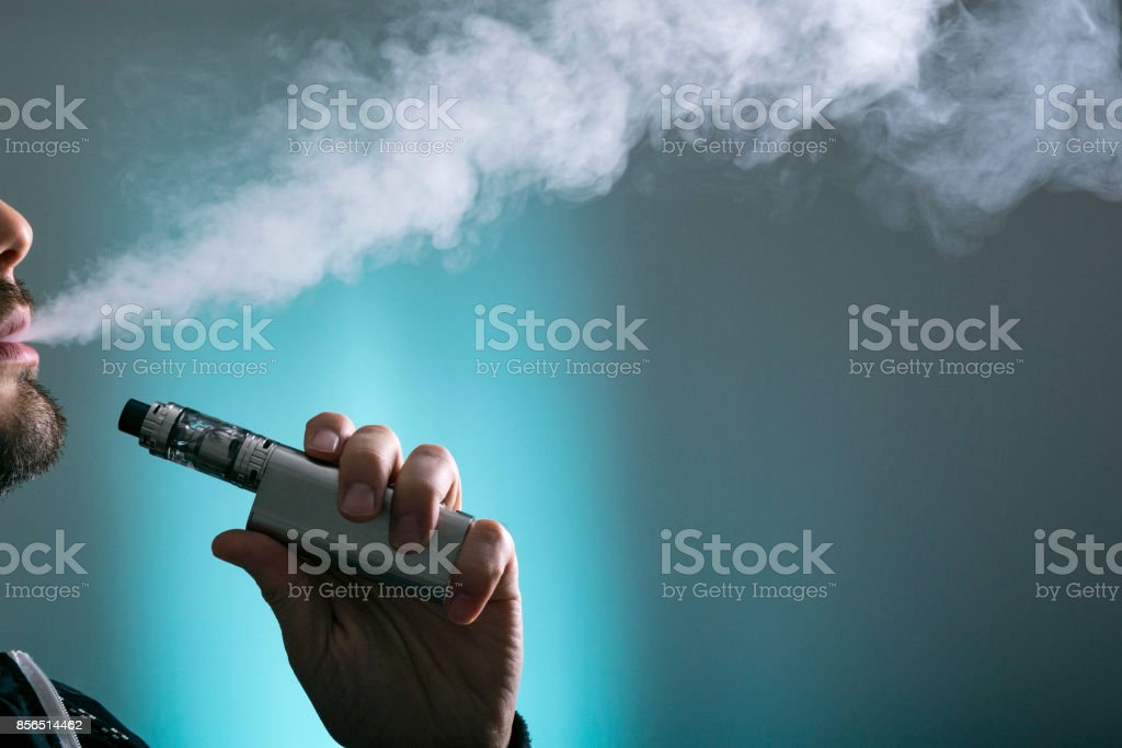 young man vape electronic cigarette cloud by using a mod, smoke tricks of vaping device background. stock photo