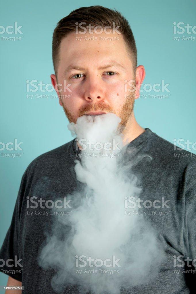 Young man vaping smoking an e-cigarette zbiór zdjęć royalty-free